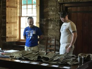 Two UCF student veterans share info on a WWI uniform during a Day of Learning at St. Augustine National Cemetery.