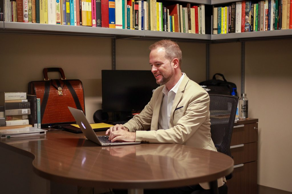 Dr. Tyler Fisher at his desk in Modern Languages and Literatures
