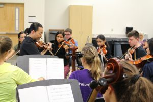 A teacher holds a string instrument while instructing students standing around him.