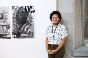 Zoraye Cyrus stands next to one of her works of art being exhibited at the ACA 30th Student Exhibition
