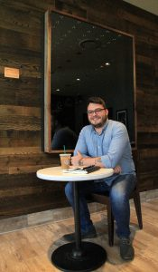 Photo of UCF alumnus Forrest Lawson '18 in front of his art at the Starbucks on Memory Mall