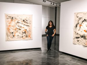 Marlenys Rojas-Reid in front of her artworks