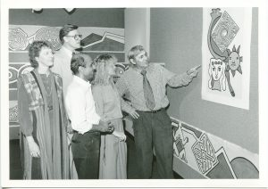 """Courtesy of UCF Special Collection & University Archives."" Professor Gaudnek showing his artwork for a group of people including Professor Chavda."