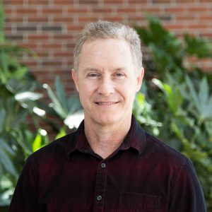 Kevin Haran: middle-aged faculty member in red and black denim shirt