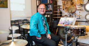 Dean Jeff Moore sits at a drumset