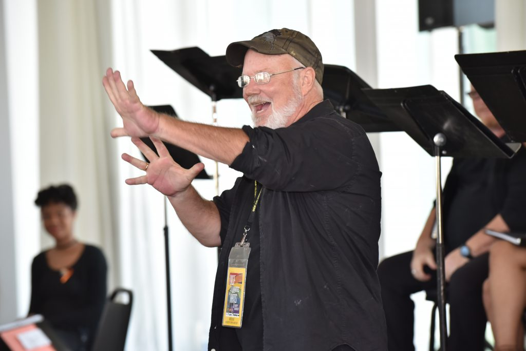 Mark Brotherton gestures enthusiastically outward from a stage.