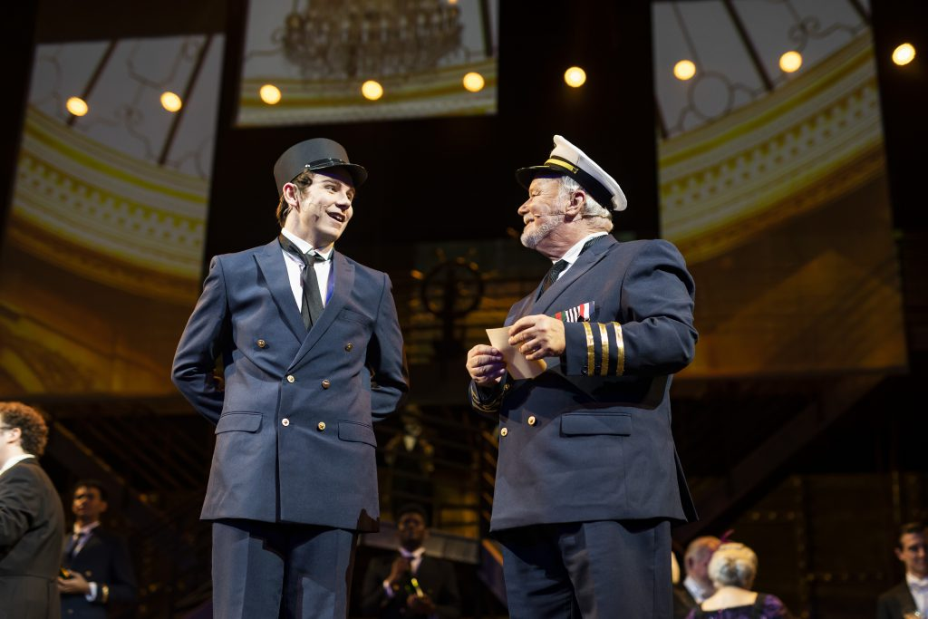Mark Brotherton performs in Titanic the Musical as the captain next to student Austin Branks