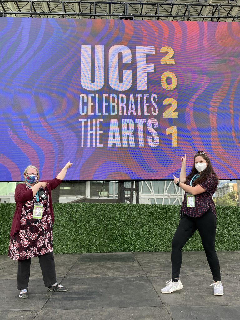 """Claudia Lynch and Lauren Koval stand on a stage pointing to a screen that says """"UCF Celebrates the Arts 2021"""""""