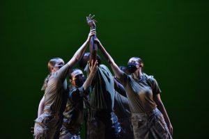 Dancers in fatigues reach upward together