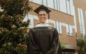 Chris Hixon stands in graduation regalia outside of Trevor Colburn Hall