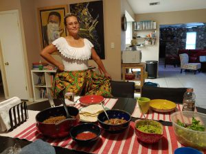 Contributing artist Wanda Raimundi-Ortiz poses in traditional clothing with the Puerto Rican food she made for her family