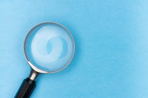 Magnifying glass on a plain blue background