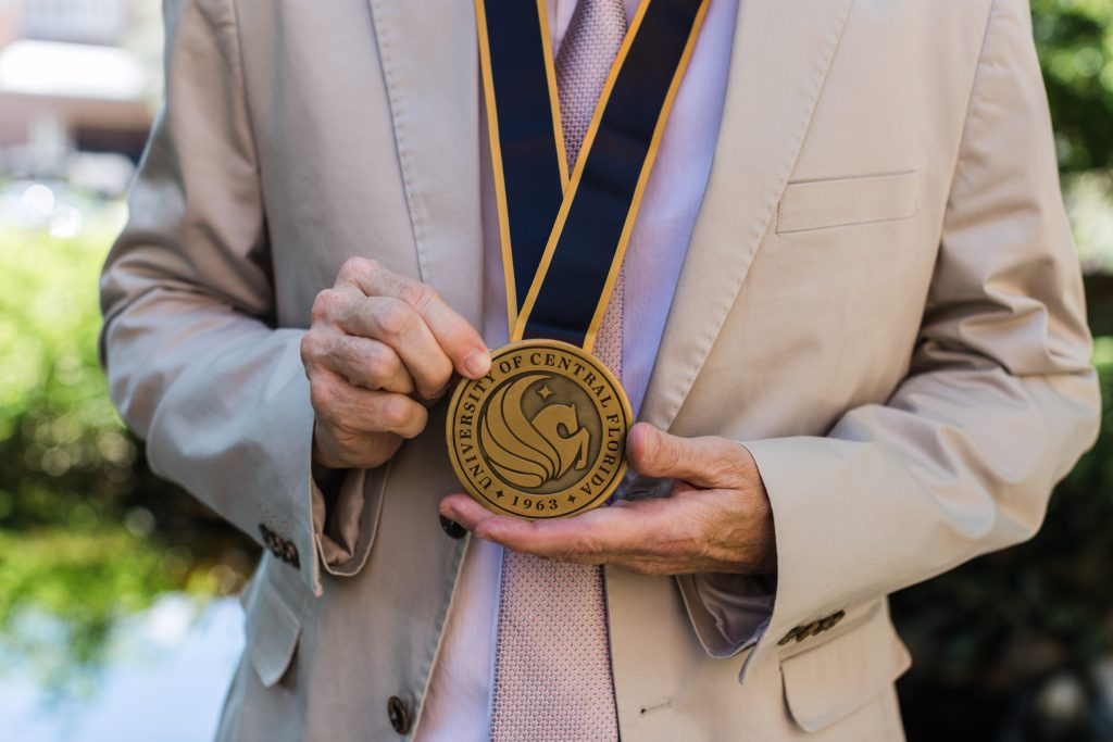 Kenneth Hanson holds the medal for his invested professorship